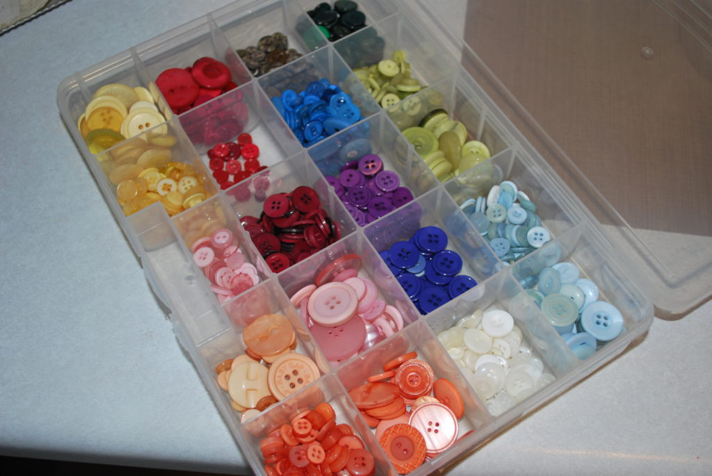 sort and store buttons in plastic divider tubs
