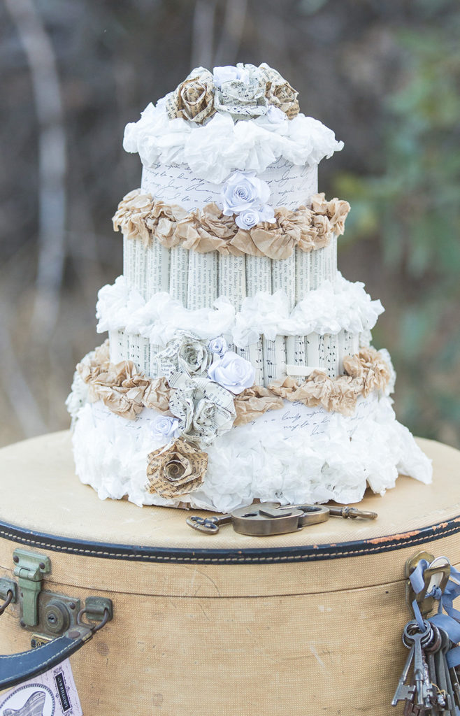Paper wedding cake staged on suitcases